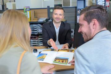 Salesman showing brochure to couple