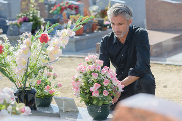 Man putting flowers on tomb