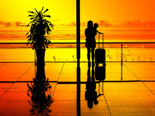 silhouette of young mother with her son with luggage standing at