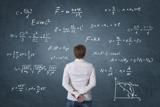Business person standing in front of mathematical formula.
