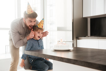 Father with birthday little son stop to covering his eyes.