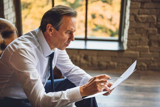 Middle aged businessman reading documents