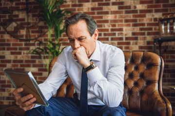Senior businessman looking at photo with deep sadness