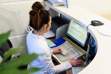 Female receptionist working the computer