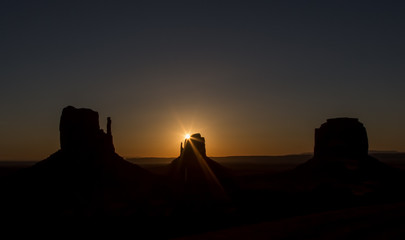 Monumental Sunrise - The sun rises behind the right mitten and creates a sun star, Monument Valley.