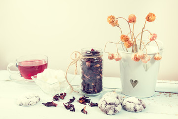 Chocolate crinkles cookies, marshmallows, Hibiscus tea, dried flowers on a light wooden table against white background. Coloring and processing photo.