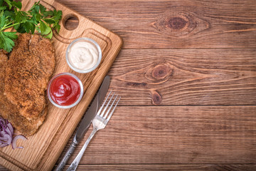 Pork schnitzel with sauce on the wooden board.