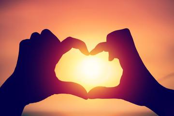 Hand making heart shape over sunset