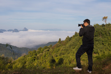 A man shooting photograph at the hill top with sea of fog and mountain view