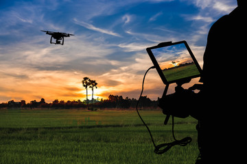 Silhouette of Man using drone to monitor the agricultural field at the evening,