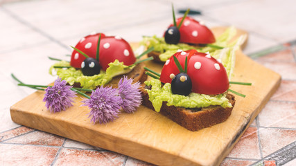 Sandwich in form of ladybird beetles made of fresh tomato, salad and bread. Funny children breakfast