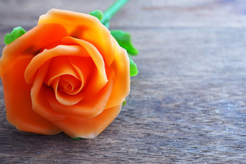 An orange rose on wooden table.