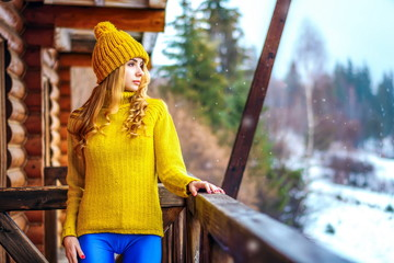 Young girl in a sweater standing on a wooden porch