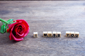 """An imprinted wood blocks displaying the word """" I MISS YOU """" with red rose on wooden background."""