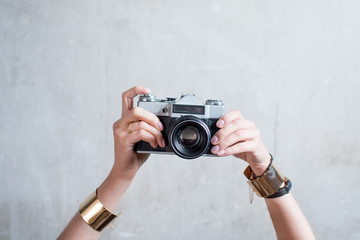 Female hands holding retro photo camera on the gray wall background