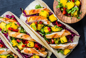 Mexican chicken tacos with vegetables and mango. Slate background