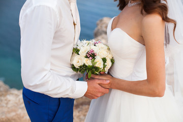 The Bride and groom holding a wedding bouquet of flowers