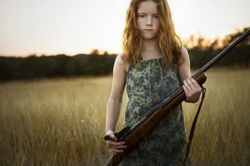 Young girl with a rifle in a field.