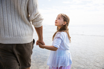 Father and daughter holding hands on a beach. Girl looks up towards father. California