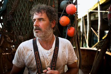 Portrait of a dirty, hard working, fisherman on boat in Portland, Maine