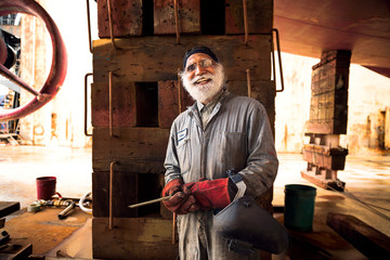 Portrait of a 55+ year old welder in a ship yard, smiling.