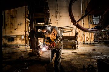 Man welding at a shipyard