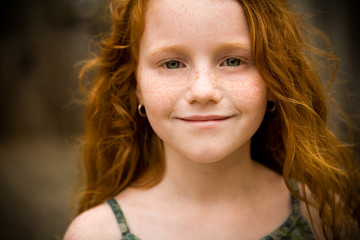 Close up of young, red-haired girl's face, smiling.