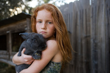Young red haired girl holding bunny