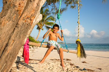 Boy smiles for the camera while swinging on a make shift log swing at beach in the Bahamas.