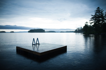 Floating dock on a lake in a rain shower