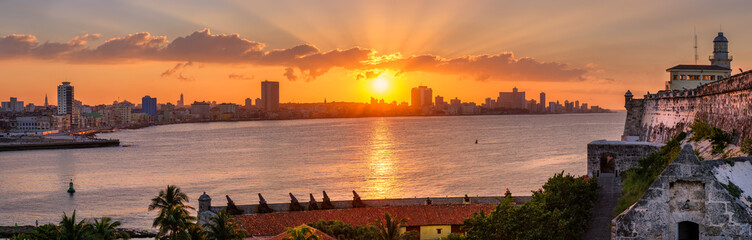 Papiers peints La Havane Sunset in Havana with the sun setting over the seaside buildings including a view of El Morro lighthouse