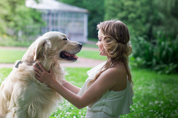 beautiful girl in white dress with a white dog in the garden