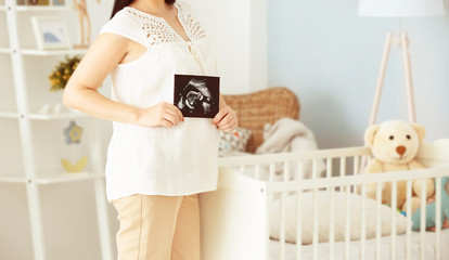 Young pregnant woman holding ultrasound photo and standing in the room