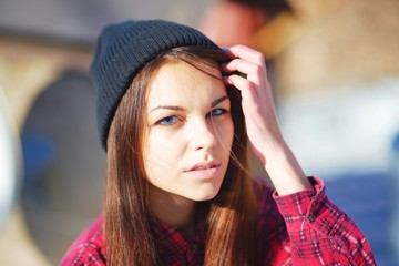 portrait of a serious beautiful girl with blue eyes, wearing a Red shirt and hat, straightens hair, on blurred background, closeup
