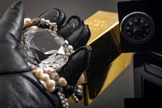 Home invasion and burglary concept with hand in leather gloves holding the loot a diamond and pearl necklace