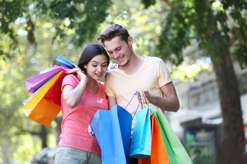 Happy couple with colorful shopping bags in park