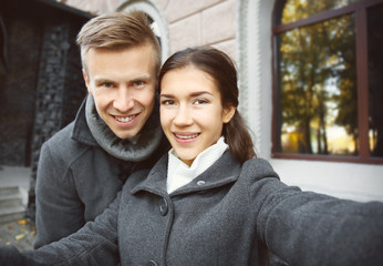 Beautiful young couple taking selfie outdoors