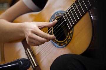 Hand girl playing guitar closeup