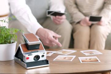 ポラロイドの写真を見るシニア夫婦の手元