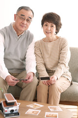 ポラロイドの写真を見るシニア夫婦