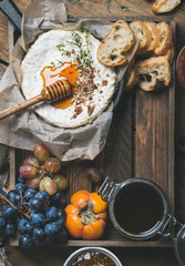Cheese, fruit and wine set. Camembert in small pan, grapes, persimmon, fig jam, honey, baguette slices and glass of rose wine over rustic wooden background, top view, copy space, vertical composition