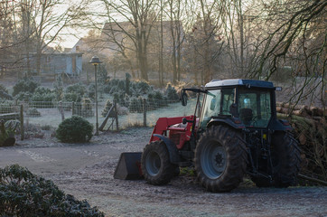 calm winter morning in the countryside with a farming tractor surrounded by bare trees