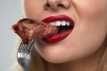 Eating Meat. Closeup Of Sexy Woman's Mouth Biting Tasty Meat