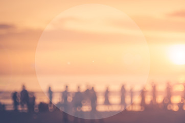 Blur people relax on tropical sunset beach with bokeh sun light wave abstract background.
