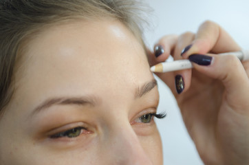 Beautiful young woman doing eyebrow correction close up