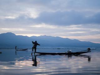 Unrecognizable fishermen in sunrise at Lake Inle