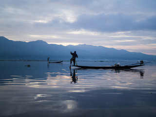 Unrecognizable fishermen in sunrise at Lake Inle