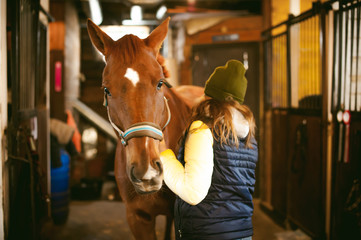 Female rider trains the horse out of the stables
