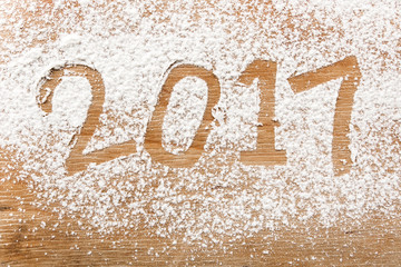 Inscription 2017 written in snow flour on the wooden background, top view