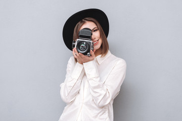 Portrait of a young smiling woman filming with retro camera